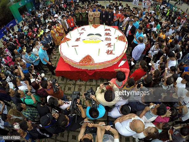 More than 100 pairs of twins and local citizens surround a large birthday cake which a cartoon twins in rafting carved on during the 10th anniversary...
