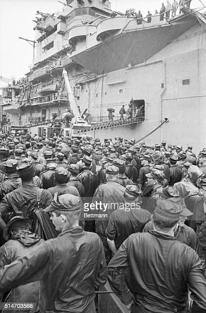 More than 1000 troops of the US 3rd Marine Division's 3rd regiment stand in the rain waiting their turn to board the USS Iwo Jima 10/6 to return to...