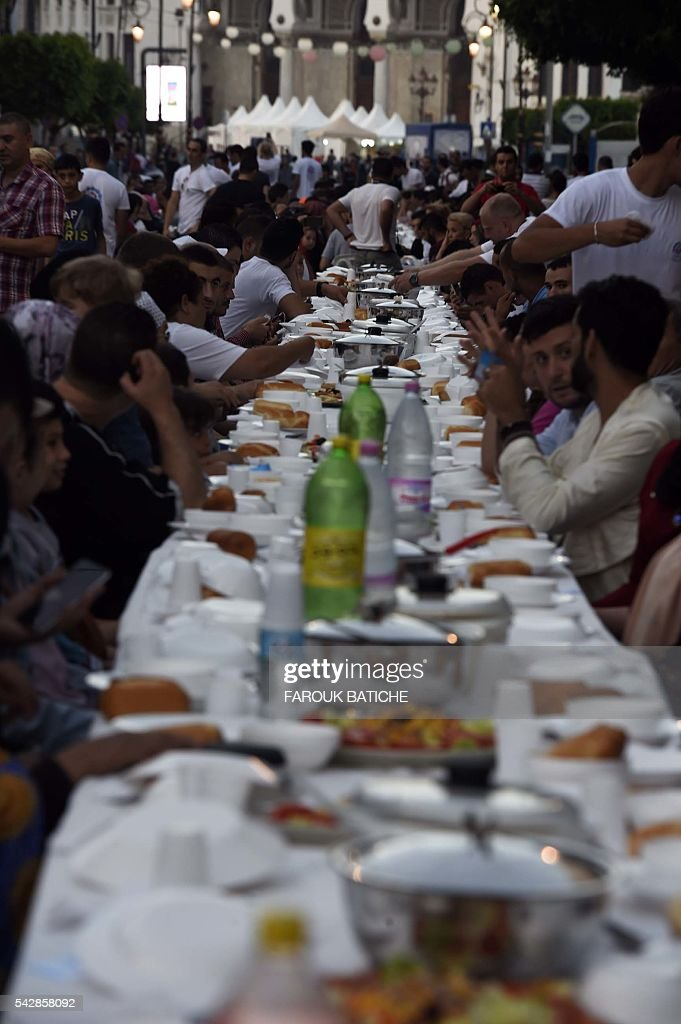 More than 1.200 people have broken the Ramadan fast with a giant meal served on Friday evening in Algiers on June 24, 2016. Along the Mourad Didouche Avenue, near the Grande Poste, hundreds of men and women of all ages, alone or with their families, famous and anonymous, gathered around big tables set on this street closed to traffic for this occasion. / AFP / Farouk Batiche