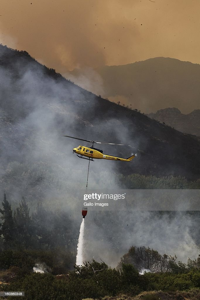 Morelug farm is water bombed by helicopter on January 29, 2013, in Paarl, South Africa. No firemen were present as the veld fire swept through the entire Boland region in the Western Cape.