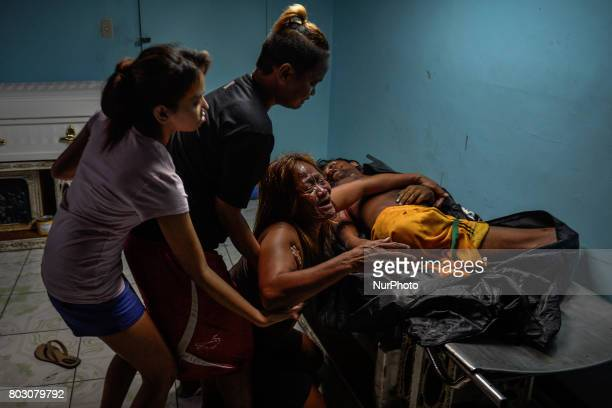 Morena Legalig weeps next to the body of her son Jerold a person with disability who was shot dead by unknown assailants during a party inside a...