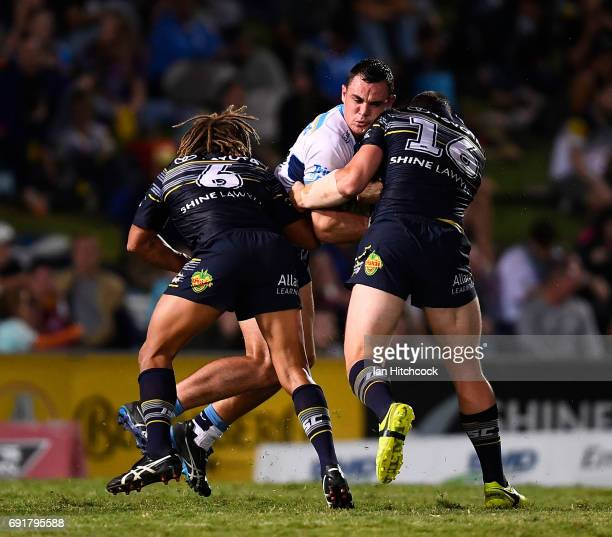 Morgan Boyle of the Titans is tackled by Ray Thompson and Shaun Fensom of the Cowboys during the round 13 NRL match between the North Queensland...