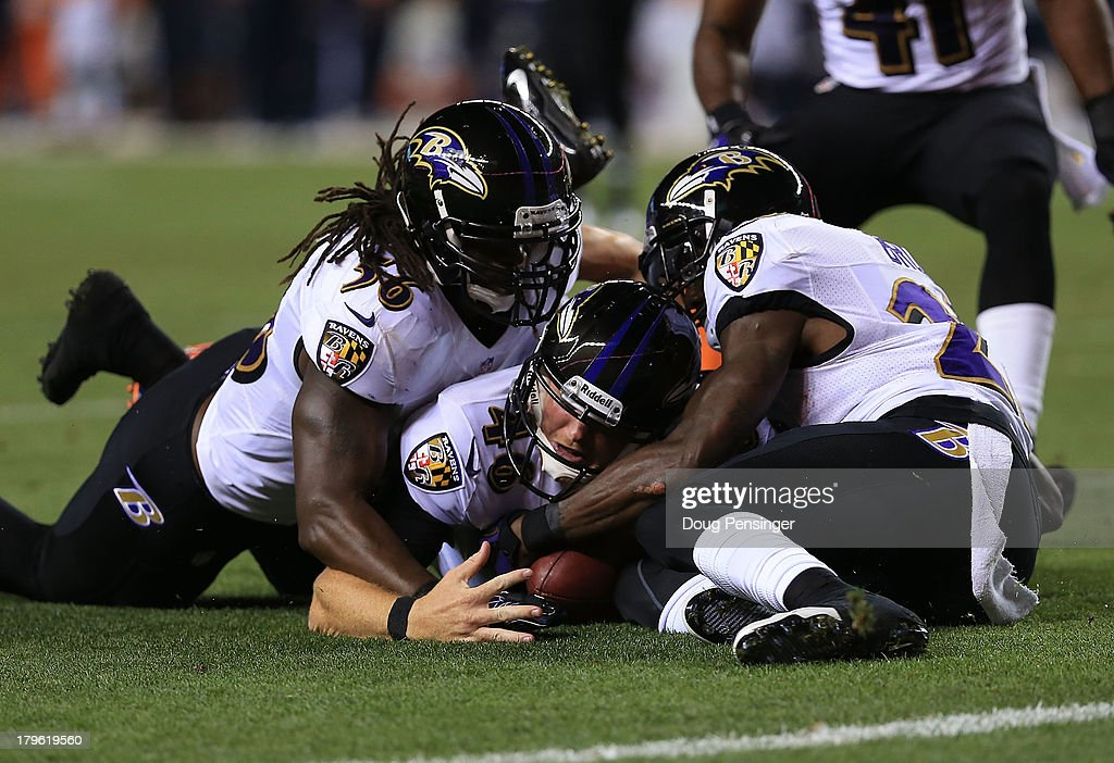 Morgan Cox Chykie Brown and Josh Bynes of the Baltimore Ravens recover a fumble by Wes Welker of the Denver Broncos following a punt in the second...