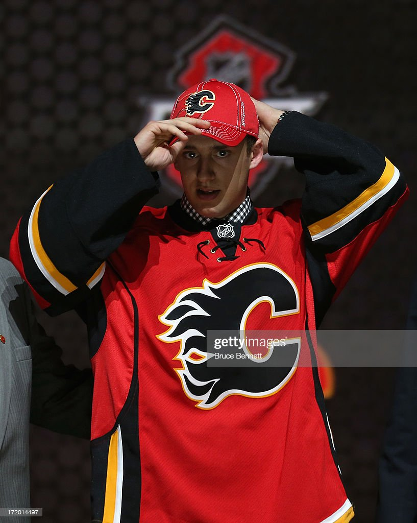 Morgan Klimchuk, drafted #28 overall in the first round by the Calgary Flames, adjusts his hat on stage after he was drafted during the 2013 NHL Draft at the Prudential Center on June 30, 2013 in Newark, New Jersey.