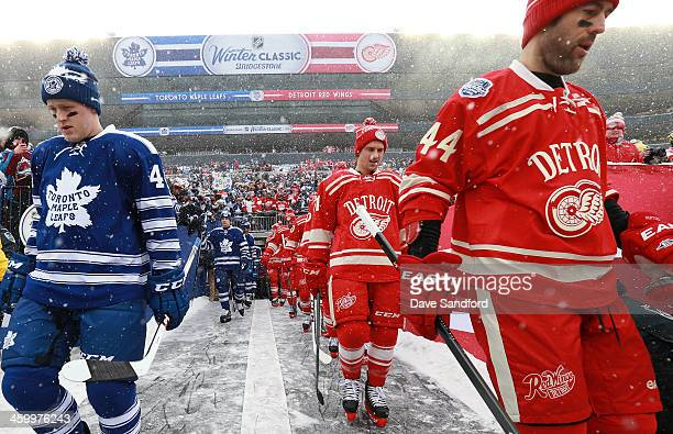 Morgan Rielly and Mason Raymond of the Toronto Maple Leafs and Luke Glendening and Todd Bertuzzi of the Detroit Red Wings make their way to the ice...