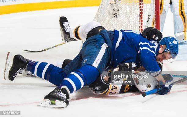 Morgan Rielly of the Toronto Maple Leafs and David Backes of the Boston Bruins collides during the first period at the Air Canada Centre on March 20...