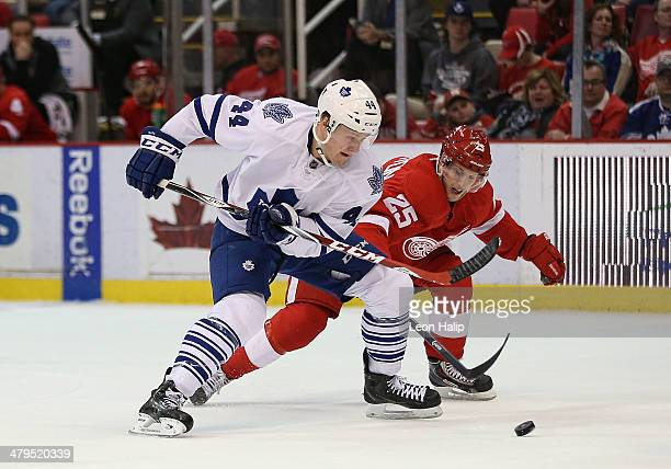 Morgan Rielly of the Toronto Maple Leafs battles for puck control with Cory Emmerton of the Detroit Red Wings during the second period of the game at...