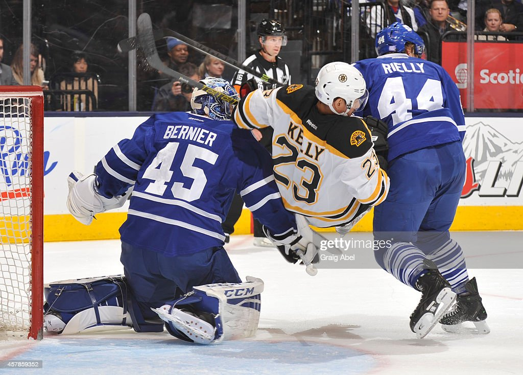 <a gi-track='captionPersonalityLinkClicked' href=/galleries/search?phrase=Morgan+Rielly&family=editorial&specificpeople=8050727 ng-click='$event.stopPropagation()'>Morgan Rielly</a> #44 of the Toronto Maple Leafs battles with Chris Kelly #23 of the Boston Bruins as teammate <a gi-track='captionPersonalityLinkClicked' href=/galleries/search?phrase=Jonathan+Bernier&family=editorial&specificpeople=540491 ng-click='$event.stopPropagation()'>Jonathan Bernier</a> #45 defends the goal during NHL game action October 25, 2014 at the Air Canada Centre in Toronto, Ontario, Canada.
