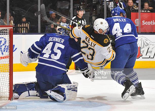 Morgan Rielly of the Toronto Maple Leafs battles with Chris Kelly of the Boston Bruins as teammate Jonathan Bernier defends the goal during NHL game...