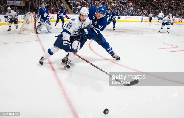 Morgan Rielly of the Toronto Maple Leafs battles with Greg McKegg of the Tampa Bay Lightning during the first period at the Air Canada Centre on...