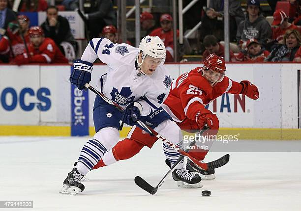Morgan Rielly of the Toronto Maple Leafs carries the puck across the blue line as Cory Emmerton of the Detroit Red Wings defends during the third...