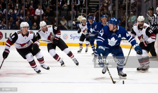 Morgan Rielly of the Toronto Maple Leafs carries the puck against Clayton Keller of the Arizona Coyotes and teammates Christian Fischer and Brad...