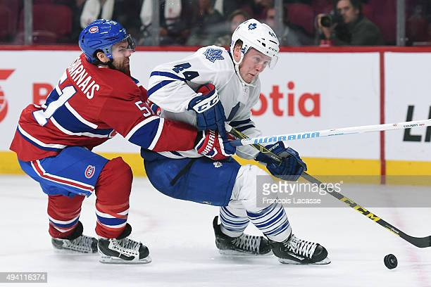 Morgan Rielly of the Toronto Maple Leafs tries to keep the puck from David Desharnais of the Montreal Canadiens in the NHL game at the Bell Centre on...