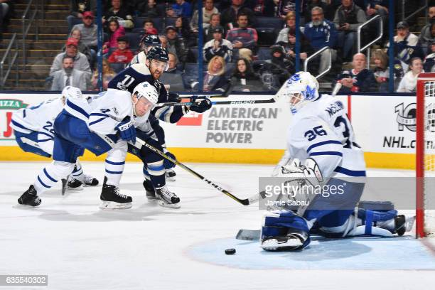 Morgan Rielly of the Toronto Maple Leafs watches as a shot by Nick Foligno of the Columbus Blue Jackets goes wide of goaltender Curtis McElhinney of...