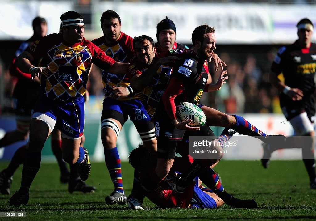 Morgan Stoddard of Scarlets is tackled by David Marty of Perpignan during the Heineken Cup Pool 5 match between Perpignan and Scarlets at the Stade...