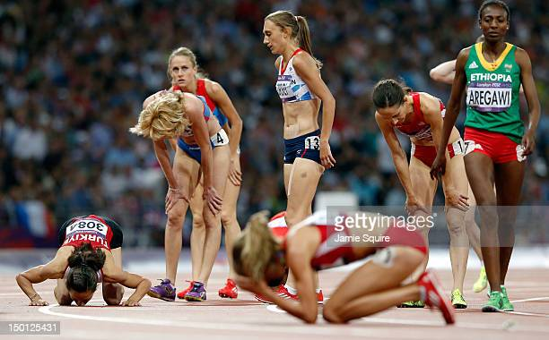 Morgan Uceny of the United States reacts after falling as Asli Cakir Alptekin of Turkey celebrates winning gold behind her during the Women's 1500m...