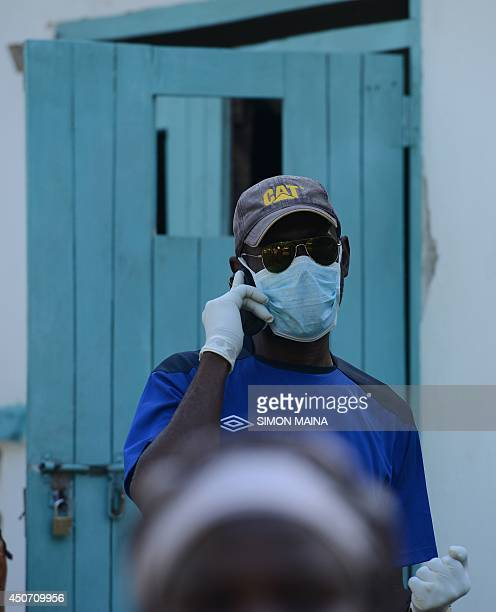 A morgue attendant speaks on a phone as he attends to bodies of victims gathered in Mpeketoni in Lamu county on June 16 after some 50 heavilyarmed...