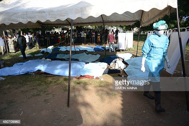 A morgue attendant walk past bodies of victims gathered in Mpeketoni in Lamu county on June 16 after some 50 heavilyarmed gunmen attacked the town...