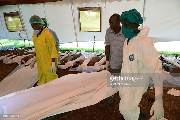 Morgue workers carry a body ready for burial at the Mpeketoni hospital in Lamu county on June 17 2014 after some 50 heavilyarmed gunmen attacked the...