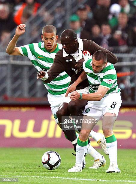 Morike Sako of St Pauli is challenged by Joshua Thompson and Scott Brown of Celtic during the friendly match between FC St Pauli and Celtic at the...