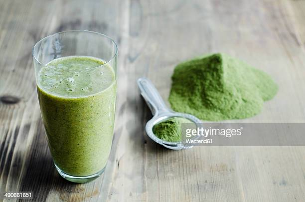 Moringa powder on spoon and wooden table and glass of moringa smoothie