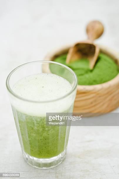 Moringa smoothie with orange and lemon juice, moringa powder in wooden bowl