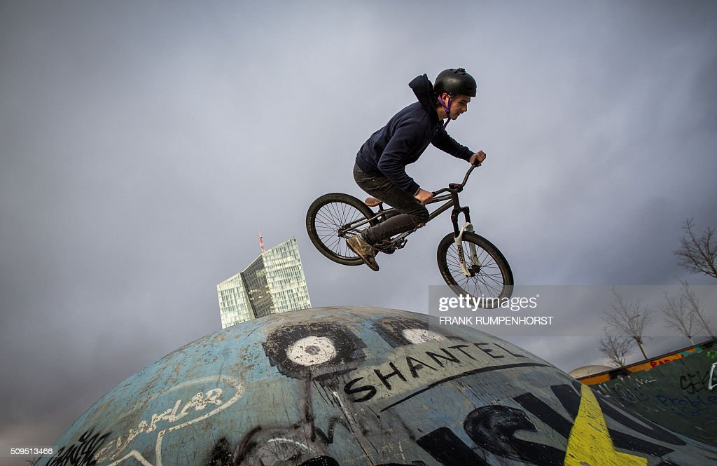 Moritz Busse practices tricks on his bike near the headquarters of the European Central Bank (ECB) in Frankfurt am Main, western Germany, on February 11, 2016. / AFP / dpa / Frank Rumpenhorst / Germany OUT