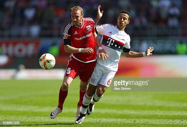 Moritz Hartmann of FC Ingolstadt and Thiago of Bayern Muenchen compete for the ball during the Bundesliga match between FC Ingolstadt and FC Bayern...