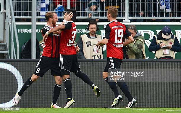 Moritz Hartmann of Ingolstadt celebrates with teammates after scoring the opening/first goal from a penalty during the Bundesliga match between FC...
