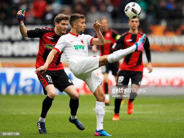 Moritz Leitner of Augsburg is challenged by Lukas Kuebler of Freiburg during the Bundesliga match between FC Augsburg and SC Freiburg at WWK Arena on...