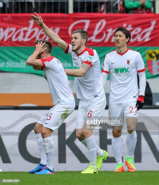 Moritz Leitner of Augsburg Jeffrey Gouweleeuw of Augsburg DongWon Ji of Augsburg gestures during the Bundesliga match between FC Augsburg and SC...