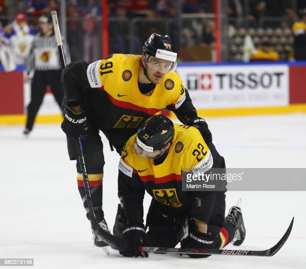 Moritz Mueller consoles Matthias Plachta of Germany after the fourth goal during the 2017 IIHF Ice Hockey World Championship game between Germany and...