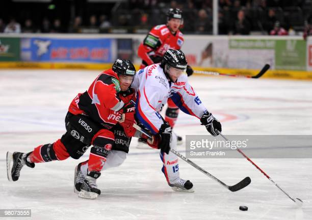 Moritz Mueller of Cologne fights for the puck with Pat Kavanagh of Ingolstadt during the DEL playoff match between Koelner Haie and ERC Ingolstadt on...