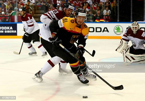 Moritz Mueller of Germany and Aleksandrs Jerofejevs of Latvia battle for the puck during the IIHF World Championship group A match between Czech...