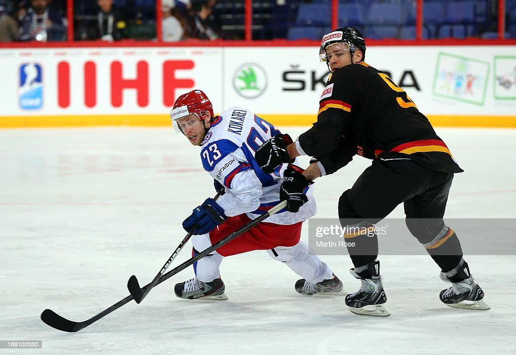 Moritz Mueller (R) of Germany and Denis Kokarev(L) of Russia battle for the puck during the IIHF World Championship group H match between Germany and Russia at Hartwall Areena on May 5, 2013 in Helsinki, Finland.