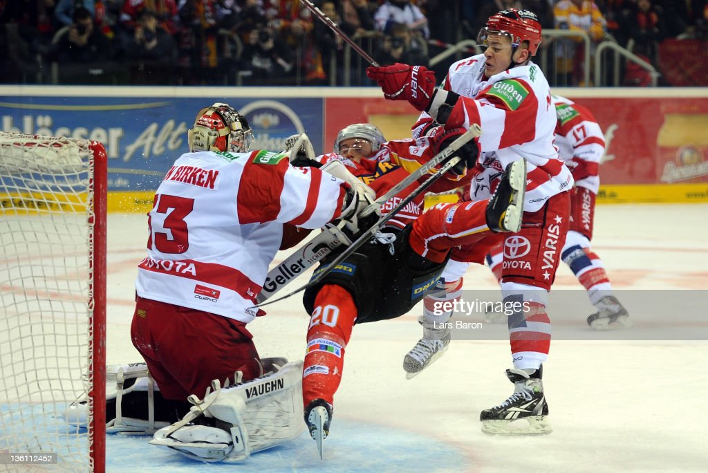 <a gi-track='captionPersonalityLinkClicked' href=/galleries/search?phrase=Moritz+Mueller&family=editorial&specificpeople=853045 ng-click='$event.stopPropagation()'>Moritz Mueller</a> of Koeln pushes Connor James of Duesseldorf into goalkeeper Danny Aus den Birken of Koeln during the DEL match between DEG Metro Stars and Koelner Haie at ISS Dome on December 26, 2011 in Duesseldorf, Germany.