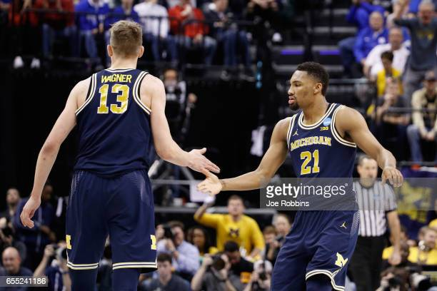 Moritz Wagner and Zak Irvin of the Michigan Wolverines show camaraderie against the Louisville Cardinals in the second half during the second round...