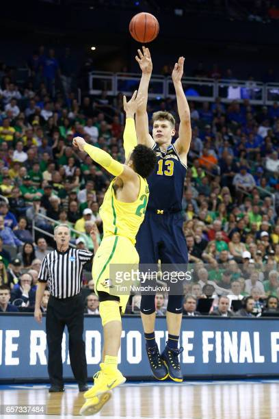 Moritz Wagner of the Michigan Wolverines attempts a threepoint shot over Dillon Brooks of the Oregon Ducks during the 2017 NCAA Men's Basketball...