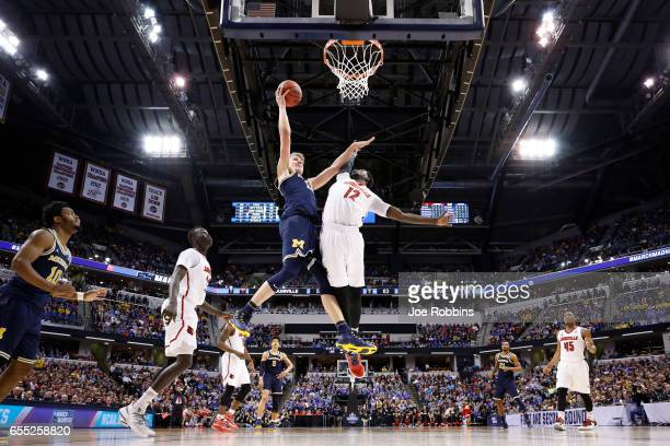 Moritz Wagner of the Michigan Wolverines drives to the basket against Mangok Mathiang of the Louisville Cardinals during the second round of the 2017...