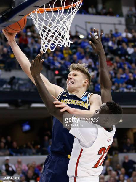 Moritz Wagner of the Michigan Wolverines shoots against Deng Adel of the Louisville Cardinals in the first half during the second round of the 2017...
