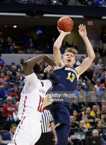 Moritz Wagner of the Michigan Wolverines shoots against Mangok Mathiang of the Louisville Cardinals in the first half during the second round of the...