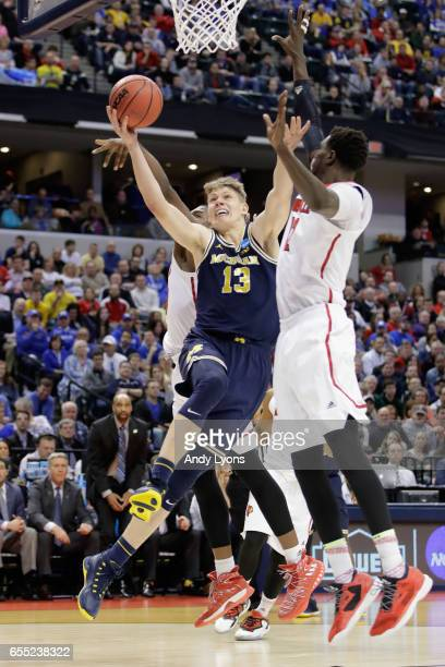 Moritz Wagner of the Michigan Wolverines shoots against Mangok Mathiang of the Louisville Cardinals in the second half during the second round of the...