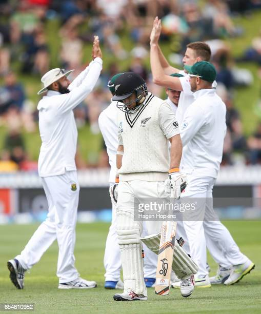 Morne Morkell and Hashim Amla of South Africa celebrate as Tom Latham of New Zealand leaves the field after being dismissed during day three of the...