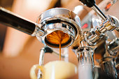 Freshly ground morning espresso coffee pouring through the bottomless portafilter of a coffee machine