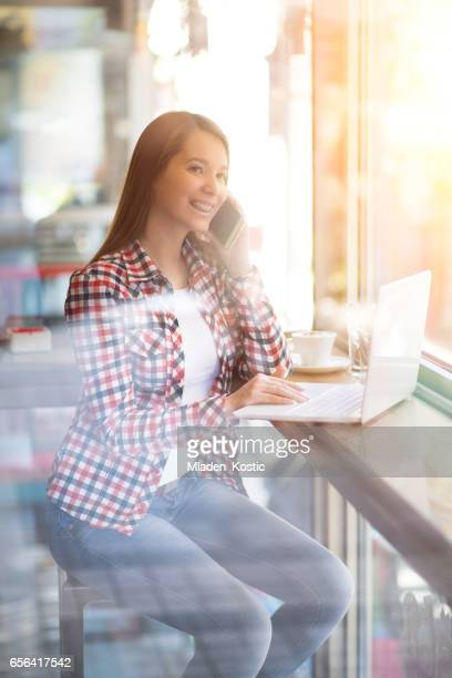 Morning Coffee, woman working on laptop an talking on phone