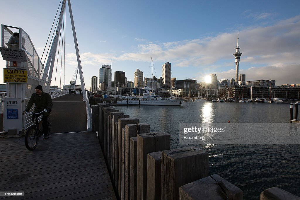 A morning commuter rides a bicycle next to the Viaduct Basin as the Sky Tower, right, stands among other buildings in the central business district in Auckland, New Zealand, on Tuesday, Aug. 13, 2013. New Zealand's growth rate is forecast to outpace Australia's for the next two years, helping stem an exodus that's resulted in the highest proportion of its people living overseas in the developed world after Ireland. Photographer: Brendon O'Hagan/Bloomberg via Getty Images