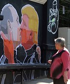 A morning commuter stops to look at a mural on a restaurant wall depicting US Presidential hopeful Donald Trump and Russian President Vladimir Putin...