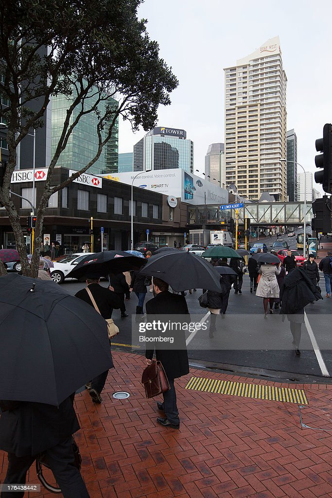 Morning commuters carrying umbrellas cross a junction in the central business district in Auckland, New Zealand, on Tuesday, Aug. 13, 2013. New Zealand's growth rate is forecast to outpace Australia's for the next two years, helping stem an exodus that's resulted in the highest proportion of its people living overseas in the developed world after Ireland. Photographer: Brendon O'Hagan/Bloomberg via Getty Images