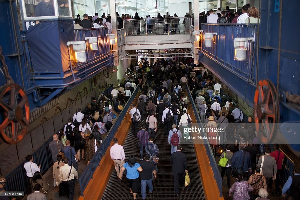 Morning commuters disembark from the Staten Island Ferry June 19, 2012 at the Whitehall Terminal in New York City's financial district. The Staten Island Ferry makes the 5.2-mile journey between the St. George Ferry and Whitehall terminals in 25-minutes and carries 21 million passengers annually.