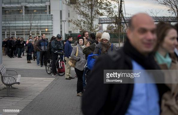 Morning commuters line up to take a Manhattanbound ferry in the Brooklyn borough of New York US on Monday Nov 5 2012 Commuters in New York and New...
